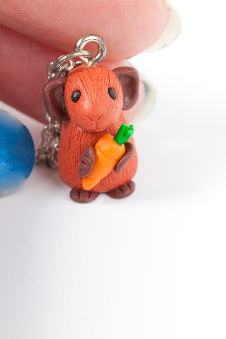 A cute hand crafted ginger guinea pig necklace. This little pig is clutching a tiny crunchy carrot. All the pets are lovingly handmade from polymer clay by Gizzys Gifts including the delicate details on the mouth, nose and fur texture.  No two characters are exactly alike so each miniature pet has its own individual personality - making them very easy to fall in love with!