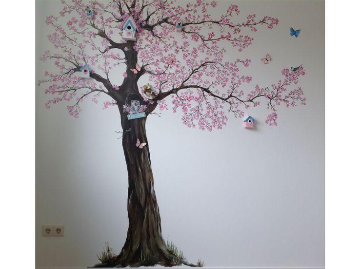Muurschildering in een kinderkamer van een grote bloesemboom met schattige vogeltjes en andere kleine beestjes. Voor een extra levendig effect zijn er zelfs echte decoraties toegepast