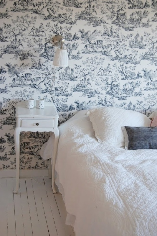 toile wall paper with fresh white painted floor boards and bedside table and white bedlinen