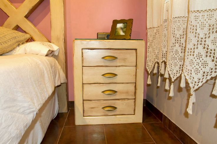Mesilla de noche de macera macisa lacada en blanco y barnizada, lo que da un color envejecido, de cuatro cajones.