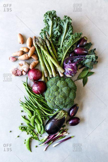 Purple and green vegetables arranged on kitchen table, vegetables, asparagus, kale, brinjals, eggplant, fresh vegetables, homegrown vegetables, spring onions, beans, peas, mangetout, broccoli, garlic, fingerling potatoes,