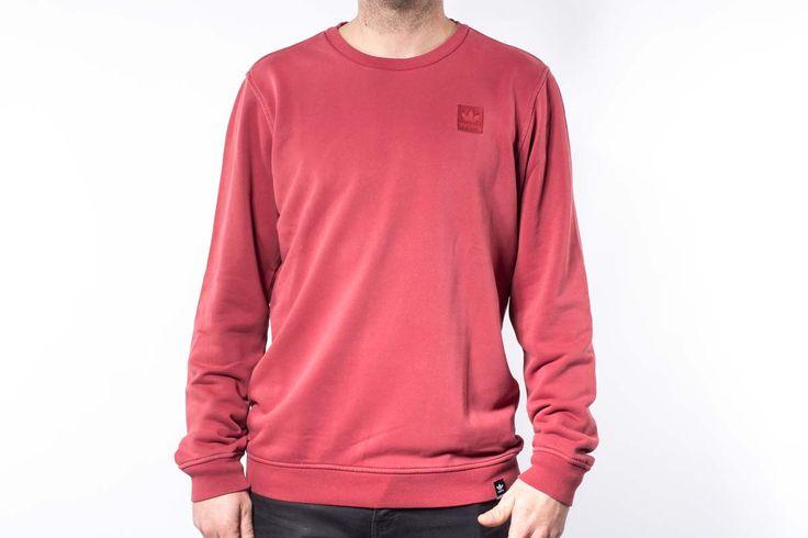 Sudadera Adidas color rojo granate, sin capucha ni cremallera, con el logo del trébol de Adidas Originals estampado en el pecho. De la línea Skateboarding Adidas Garment Dye.