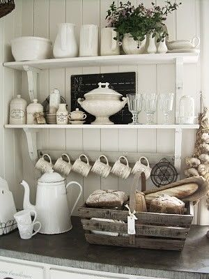 white kitchen storage wall :-) shelves, hooks, mugs, teapot, bread