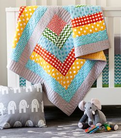Boo's Nursery baby room quilt patterns featured in Quilty July/August 2013 include baby quilt, curtain, changing pad cover, crib sheet and crib skirt patterns. Quilt by Kristi Loeffelholz for Quilty July/August 2013.