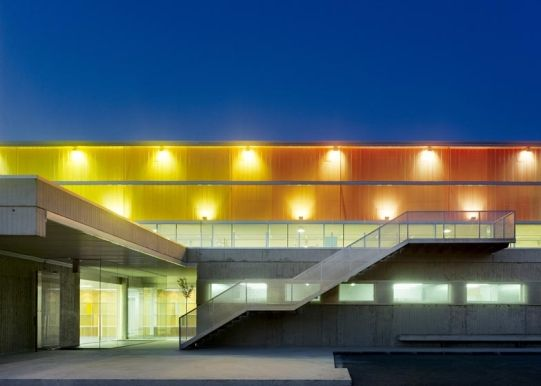 """Architecture: Pazo dos Deportes de Arteixo (Sports Centre) by José Ramón Garitaonaindía de Vera: """"..a rainbow of coloured panels extend up from a concrete base to form the walls of this sports hall..The walls of the building enclose a small square courtyard near to theentrancelobby, as well as anotherstretchingalongside the games hall..An external staircase leads up to a first floor terrace, where visitors can observe activities taking place inside.."""" Luminous.."""