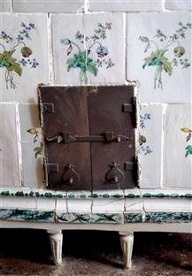 Close up of old Swedish tiled stove with flower decor