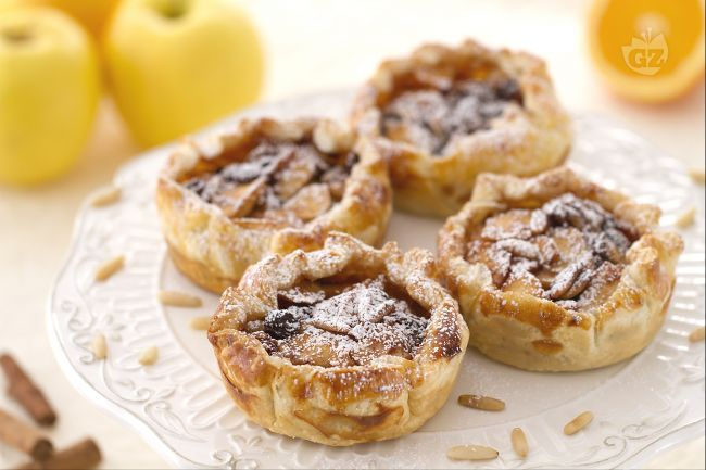 Le tortine di mele in sfoglia sono un delizioso dessert, semplice e ideale per un fine pasto, con cestini di pasta sfoglia, mele e uvetta.