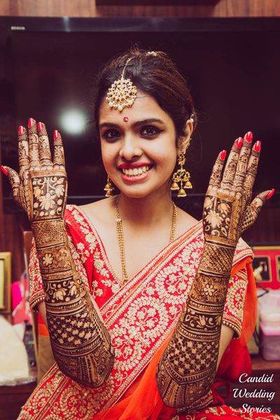 South Indian Brides - South Indian Bride in an Orange and Red Saree with Bridal Mehendi Design | WedMeGood #wedmegood #southindianbride #mehendi #mehendidesign #bridal #southindianwedding #henna #tattoo