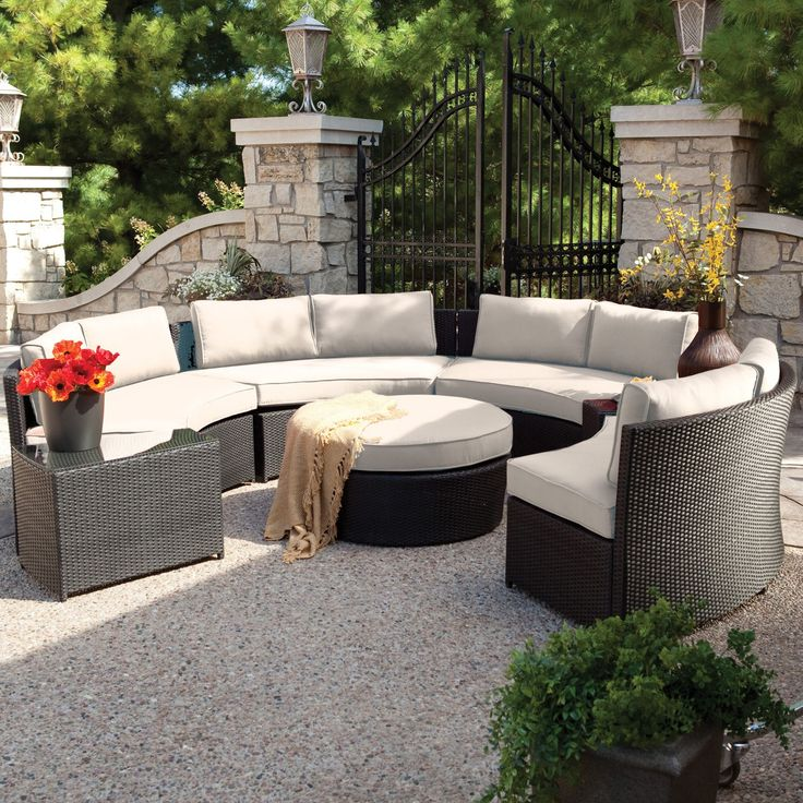 Large, circular conversation patio sectional features high contrast between dark resin wicker construction and off-white cushioning. Centering around a large, circular ottoman, the set includes a wedge shaped, glass top table.
