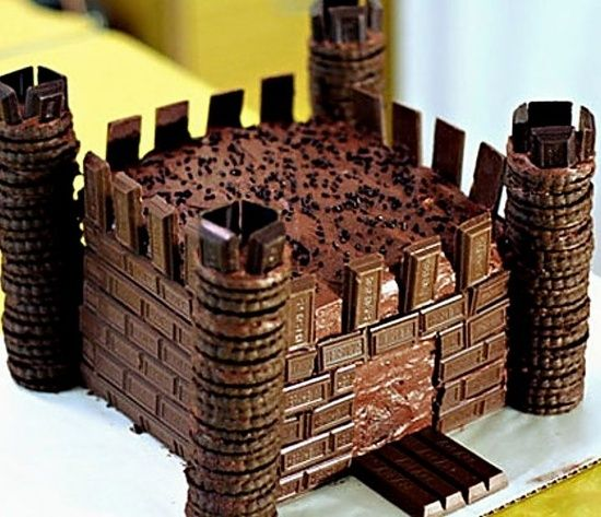 Fun IDEA !! Castle Cake… 2 square cakes on top of one another with icing, …. cookies for the towers,( a wee bit of icing in between cookies for gluing them together ) chocolate bar pieces for brick … kit kat chocolate slab for Drawbridge.