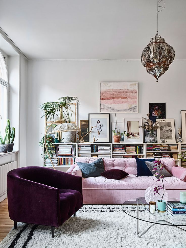 Chic bohemian decor in a living room design featuring a pink velvet sofa, a deep purple chair, white bookcases and layers of art in black, white, gray, and pink - Modern Global Decor & Boho decorating Ideas - Home Tour: the glamorous home of Amelia Widel — The Decorista