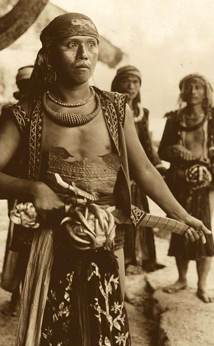Noble warrior from South Nias wearing an impressive gold 'nifitali-tali' necklace and a large 'balatö' sword.  He also wears a collection of crocodile teeth.  ca. 1930 ||| Source; Ethnic Jewellery from Indonesia: Continuity and Evolution. Bruce W Carpenter. Pg 48