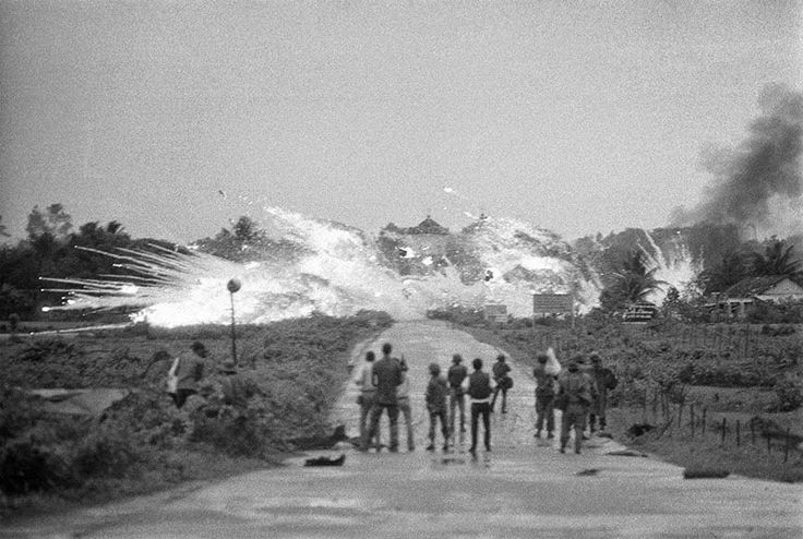 Bombs with a mixture of napalm and white phosphorus jelly dropped by Vietnamese  AF Skyrider bombers explode across Route 1 amid homes and in front of the Cao Dai Temple in the outskirts of Trang Bang, on June 8, 1972. In the foreground are Vietnamese soldiers, news and cameramen from various international news organizations watching.  ~ Vietnam