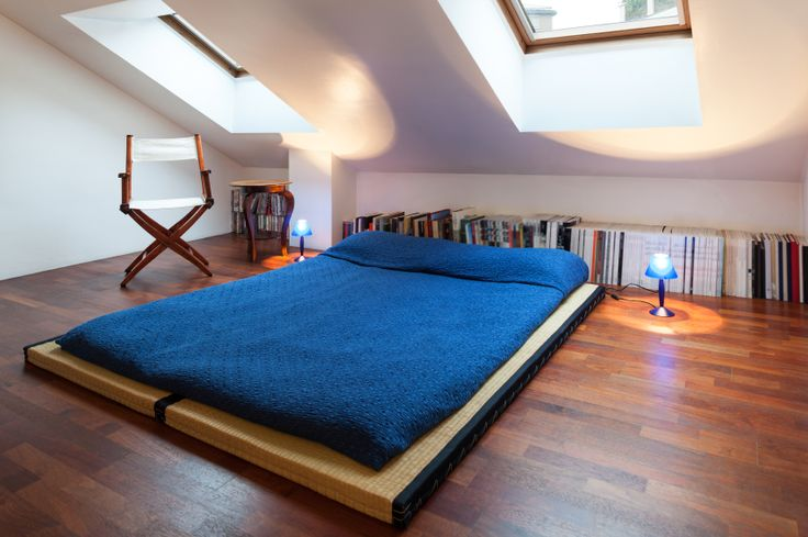 A simple bedroom on a tatami mat and a row of books along the back wall.
