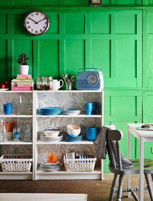 布地で個性的にデコレーションしたBILLY/ビリー 書棚がシンプルなインテリアのアクセント。棚板にカラフルな食器セットをディスプレイしたダイニングルーム。