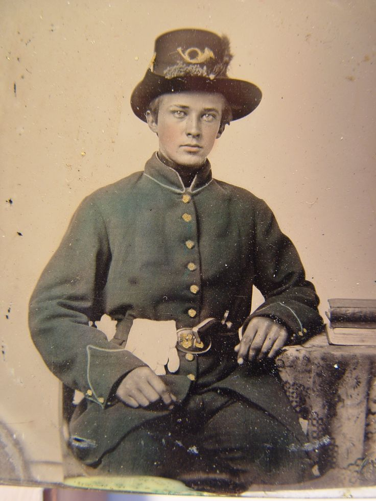 Unidentified young soldier in Union uniform and plumed Hardee hat with plain gauntlets and revolver sitting next to table with books.  From: Soldiers of the Civil War.