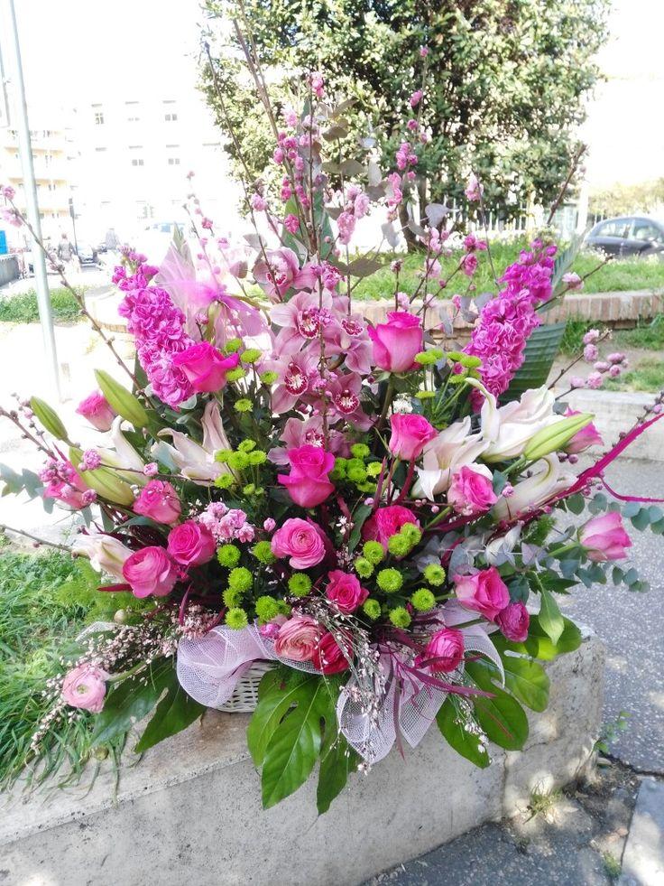 Raffinata composizione in cesto con rose rosa, fiore di orchidea, fiori di pesco e violaciocca   abbellita da verde misto.