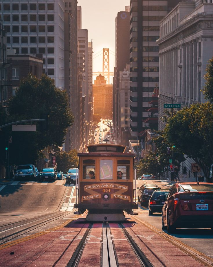 grey cable car between buildings San francisco pictures