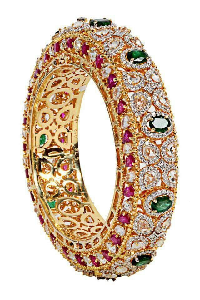 Beautiful gold kangan studded with diamonds and precious stones.