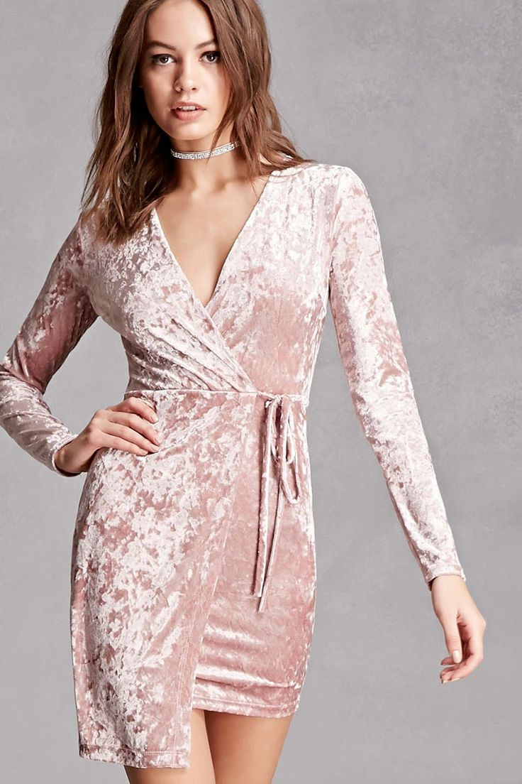A knit crushed velvet dress featuring a mock wrap front with self-ties, a surplice neckline, long sleeves, a back button keyhole back, and an asymmetrical hem. This is an independent brand and not a Forever 21 branded item.