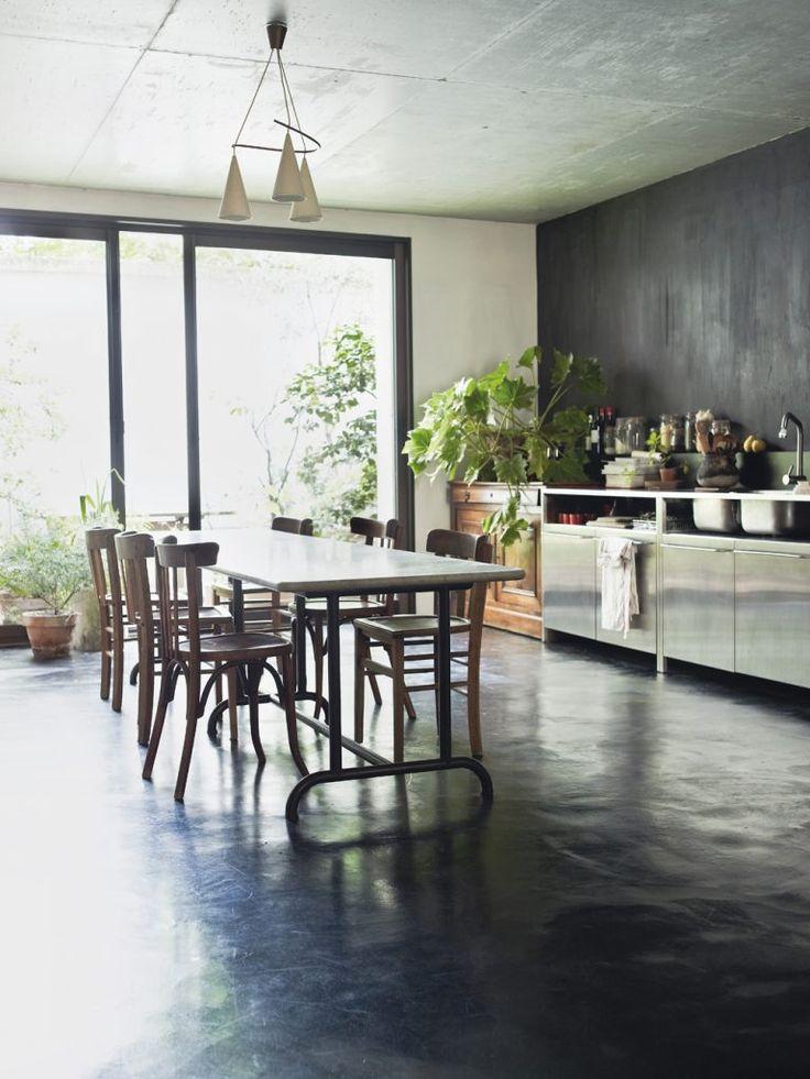 Fransk bistrokänsla i köket. Brunsvart köksinredning från Ikea, stor köksö, fasade vita kakelplattor från Rojan kakel & interiör, rostfria vitvaror och en betongbänkskiva. Taklampa Ikea, betongljusstake Tove Adman. Foto: Daniella Witte