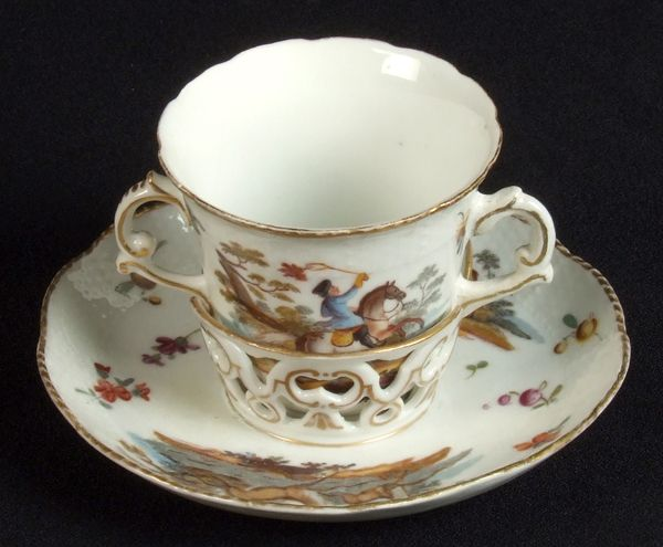 MEISSEN TREMBLEUSE CUP AND SAUCER. Meissen porcelain trembleuse cup and saucer, double handled cup with hand painted cartouches of hunters, saucer with trembleuse holder decorated with two cartouches of deer in forest. Marked: Crossed swords mark over M.