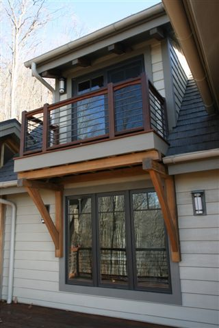 A second level balcony porch is supported by timber frame brackets on Dave & Jean's NC home.