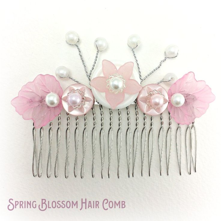 Pink bridal flower hair comb embellished with buttons topped with silver bead caps, pearl effect beads and pink lucite leaves