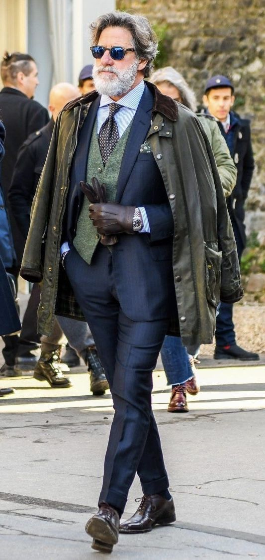 Fall outfit layering inspiration with a green waistcoat navy suit blue striped shirt brown silk patterned tie sunglasses brown gloves watch brown/olive jacket dark brown shoes. model unknown.  #suit #menswear #gentlemen #classy #menstyle #mensfashion #waistcoat #coat – Toni