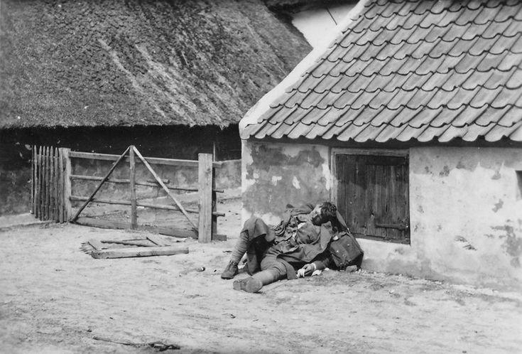 Gesneuvelde Nederlandse militair bij een boerderij - 15-16 mei 1940 Duitse opname van een gesneuvelde Nederlandse militair, gemaakt in de Nude (tussen Wageningen en Grebbeberg) of ten Noorden van de Grebbeberg (omgeving Achterberg).