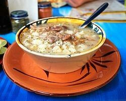 """Pozole (Nahuatl: pozolli Spanish pronunciation: [po'solːi], modern Nahuatl prounciation Listen, variants: pozolé, pozolli, pasole),[1][2][3] which means """"hominy"""", is a traditional soup or stew from Mexico, which once had ritual significance. It is made from hominy,[1] with meat (typically pork), and can be seasoned and garnished with shredded cabbage, chile peppers, onion, garlic, radishes, avocado, salsa and/or limes.[4]  It is a typical dish in various states such as Sinaloa, Michoacán…"""