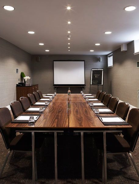 Meeting Room. Table with chairs along the sides, and projector/activboard.:
