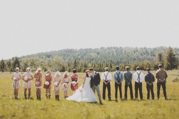 Idaho Woodsy Wedding - I LOVE HOW THE BRIDAL PARTY IS TURNED AWAY WHILE THE BIDE AND GROOM SMOOCH FACING THE CAMERA. SO CUTE!