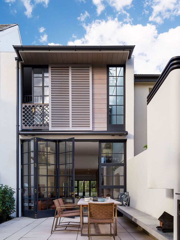 This modern row house an internal courtyard at the rear of the home accessed through the main floor. A built-in bench provides seating for an outdoor dining table.