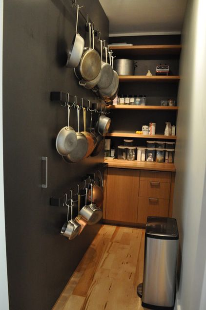 by Rebekah Zaveloff | KitchenLab. Put your hallway or pantry door to work with a little hangers to hang pots and pans.