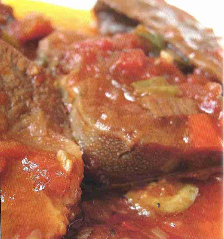 Lengua de res guisada Ingredientes 1 lengua de res, unos 750 gramos 1 limón 5 tazas de agua la parte blanca y algo de lo verde de 1 ajo porro y de una rama de celeri 1 cebolla cortada en dos 1/2 pimenton verde 2 dientes de ajo machacados 2 cucharaditasde sal 3 o 4 granos enteros de pimienta negra 1 taza de tomate picado sin piel y sin semillas 2 tazas de cebolla picada 1/2 pimentón rojo 3 diientes de ajo, machacados 1/3 de taza de aceite