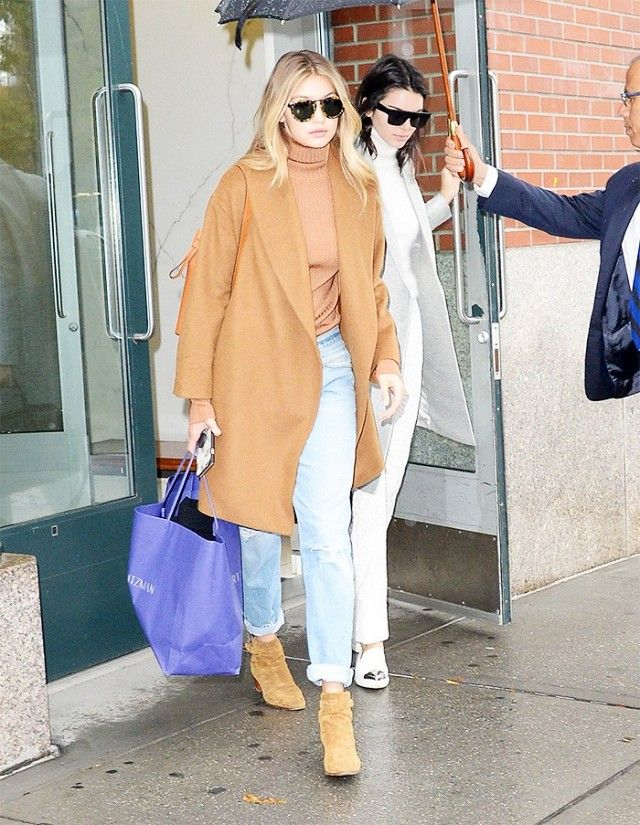 Gigi Hadid wears a camel coat and sweater with jeans and Saint Laurent suede ankle boots.