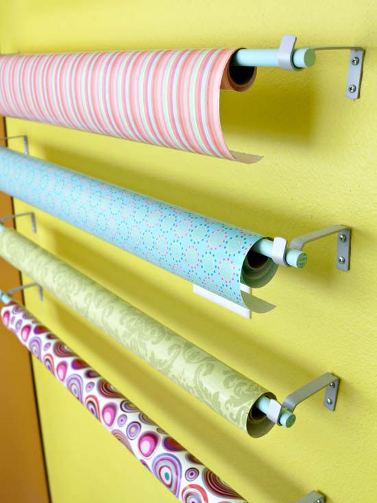 It's A Wrap        It couldn't get much simpler. Dowel rods suspended from inexpensive curtain hardware allows easy access to wrapping and crafts papers. She painted the dowels blue to align them with her color palette.