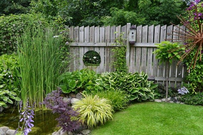 So many things to love in this garden: the pond, the fence peep hole, the rusted sculpture and the beautiful plantings