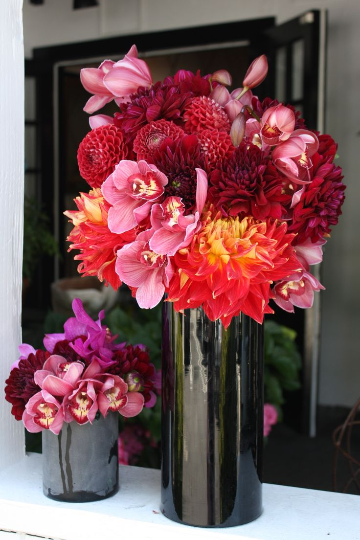 "This dramatic black vase is offset with orange ""dinner plate"" dahlias, deep red dahlis and mauve cymbiduym orchids - by Botany Flowers"