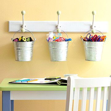 Metal buckets hanging from coat rack for kids craft supplies