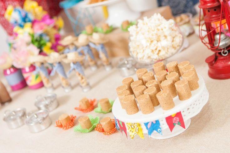 Outro varal com minibandeiras foi usado para decorar suportes de doces, que enfeitaram a mesa da festa de aniversário com tema junino