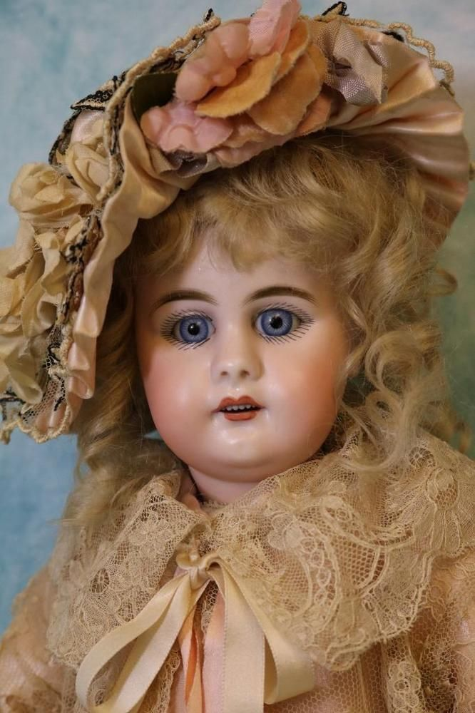 Antique 17.5 Inch 949 Simon & Halbig Brilliant blue glass sleep, with original Body that is signed on back Germany 2. This is an especially pretty Simon & Halbig 949 German bisque doll. She has blue spiral threaded glass sleep eyes, delicately painted upper and lower lashes, finely painted brushstroke eyebrows, open mouth with teeth, accented nostrils, dimpled chin and pierced ears, cardboard pate, and antique blond mohair wig. Antique composition body with jointed wrists, and origina...