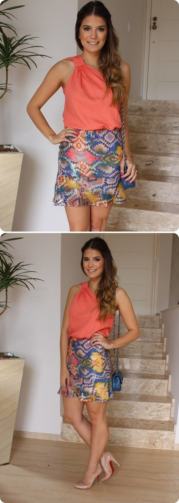 Smiling tanned chocolette in coral off-shoulder sleeveless blouse, colourful patterned miniskirt, blush stillplats w/ red soles