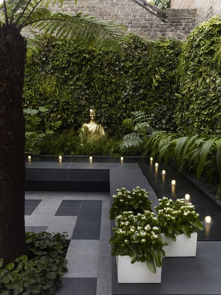 Dering Hall. Terrace with gray stone tiles, gold Buddha, square white planters, ivy walls and lighted water feature. Pic 16 in slideshow: