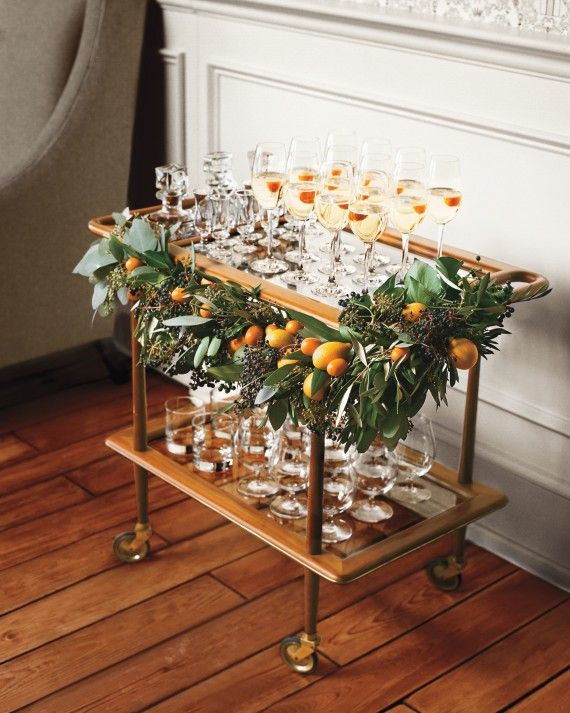 """Champagne is practically synonymous with celebrating. Create a cozy Champagne bar by adorning a wheeled cart or stationary bar with a bountiful in season garland. Florist Jackie Reisenauer of Minneapolis' Munster Rose created this with privet berries, bay leaves, and kumquats. Winter wedding? Use amaryllis, anemones, paperwhites, seeded eucalyptus, stephanotis, or tulips. As Reisenauer points out """"it's very affordable, relying only on foliage and fruit."""""""
