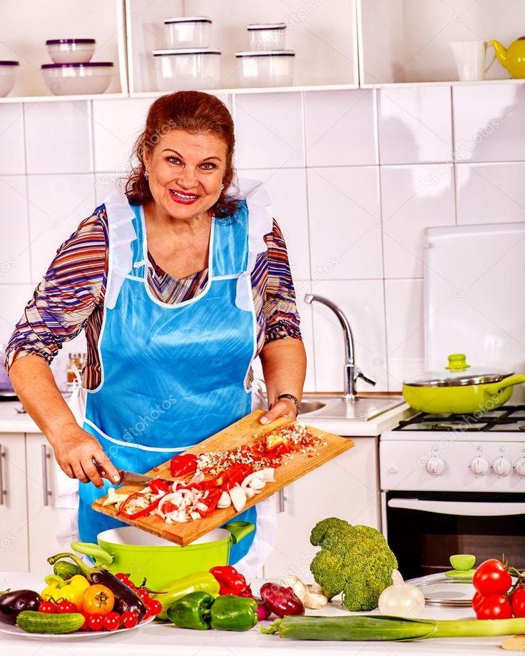 Elderly woman prepares food in the kitchen. Stock Photo