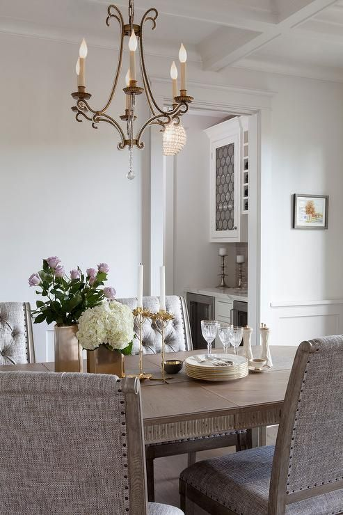 Hung From A Coffered Ceiling, An Oslo Chandelier Is Fixed Above A Honey  Stained Oval Dining Table Topped With Brass Vases And Candle Holders And  Surrounded ...