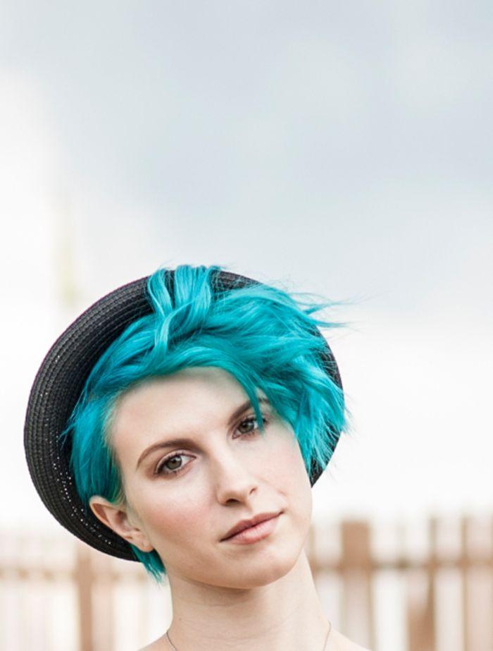 türkise Haare, Kurzhaarfrisur für Damen, schwarzer Hut, natürlicher Make up, helle Haut