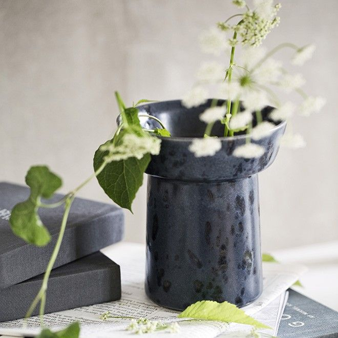 Discover Ombria - a vase by Anders Arhøj who drew his inspiration for the rough stoneware range from the wild Scandinavian countryside. The small moonlight blue vase features the exciting glaze applied by hand in deep blue, which evokes the dark ocean during a storm. Create a beautiful contrast with bright, delicate flowers or fresh green branches and let the calm colours of the vase set off the shades in the plants.